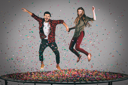 midair: Fun in motion. Mid-air shot of beautiful young cheerful couple holding hands while jumping on trampoline together with confetti all around them