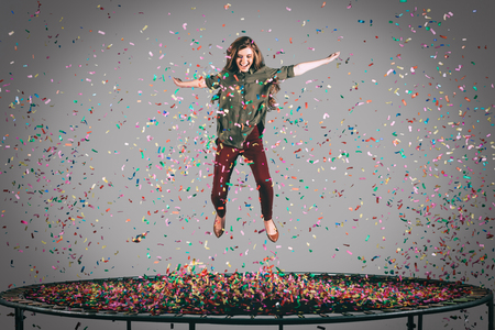 midair: Beauty on trampoline. Mid-air shot of beautiful young woman jumping on trampoline with confetti all around her Stock Photo