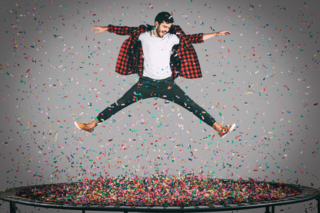 midair: Carefree fun. Mid-air shot of handsome young man jumping on trampoline with confetti all around him