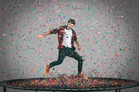midair: Trampoline and confetti. Mid-air shot of handsome young man jumping on trampoline with confetti all around him