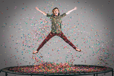 Like a star. Mid-air shot of beautiful young woman jumping on trampoline with confetti all around her