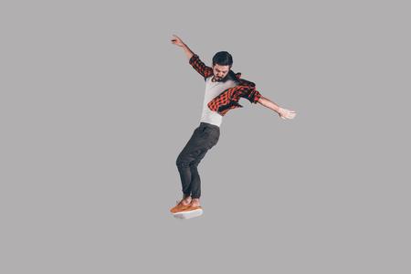 Sensación de libertad en cada movimiento. disparo en pleno vuelo de Salto del hombre joven y guapo y haciendo un gesto contra el fondo