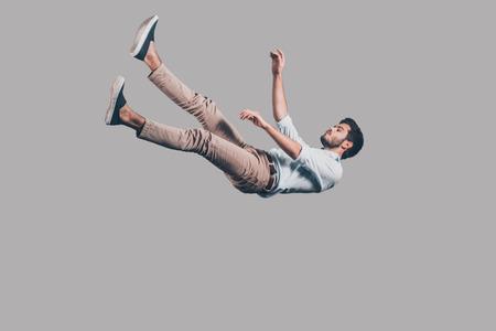 Hombre que cae abajo. disparo en pleno vuelo de apuesto joven que cae sobre fondo gris