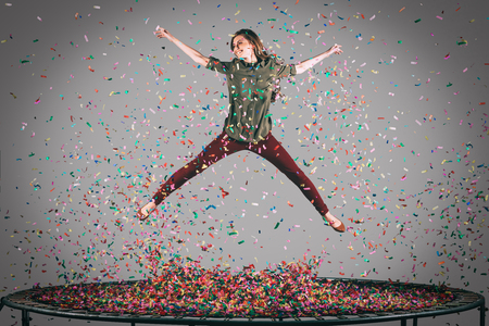 super star: Like a super star. Mid-air shot of beautiful young woman jumping on trampoline with confetti all around her