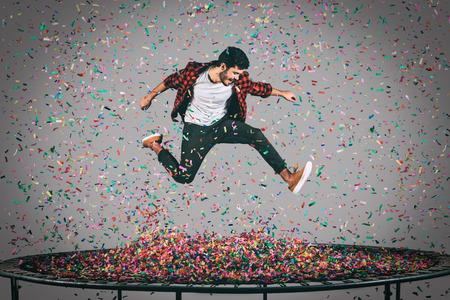 明るい生活を。ハンサムな若者は、すべて彼の周りに紙吹雪をトランポリンでジャンプの空中ショット