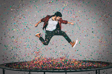 Living a bright life. Mid-air shot of handsome young man jumping on trampoline with confetti all around him Stock Photo