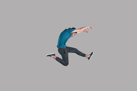 midair: Freedom in moving. Mid-air shot of handsome young man in cap jumping and gesturing against background Stock Photo