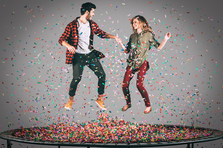 midair: Colorful fun. Mid-air shot of beautiful young cheerful couple holding hands while jumping on trampoline together with confetti all around them Stock Photo