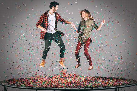 people jumping: colorida de la diversión. disparo en pleno vuelo de hermosa pareja alegre joven de la mano mientras salta en el trampolín junto con confeti a su alrededor