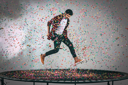 midair: Mid-air fun. Mid-air shot of handsome young man jumping on trampoline with confetti all around him