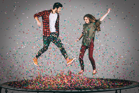 midair: Confetti fun. Mid-air shot of beautiful young cheerful couple jumping on trampoline together with confetti all around them Stock Photo