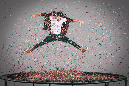 moda ropa: Diversión en movimiento. disparo en pleno vuelo de apuesto joven que salta en el trampolín de confeti a todos a su alrededor