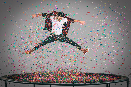 fashion clothes: Fun in motion. Mid-air shot of handsome young man jumping on trampoline with confetti all around him Stock Photo