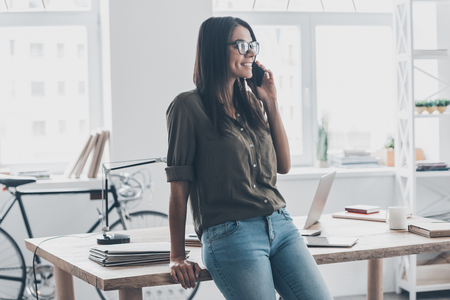 confident woman: Good business talk. Confident young woman in smart casual wear talking on the mobile phone and smiling while standing near her working place Stock Photo