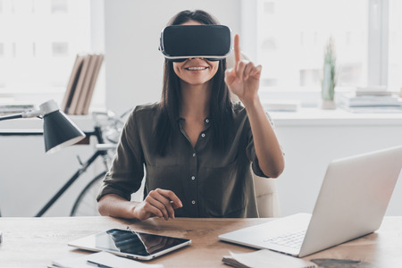 it: It seems so real. Confident young woman in virtual reality headset pointing in the air while sitting at her working place in office