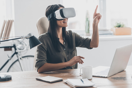 interactivity: Using VR technologies. Confident young woman in virtual reality headset pointing in the air while sitting at her working place in office
