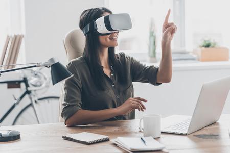 VR 기술 사용. 사무실에서 그녀의 작업 장소에 앉아있는 동안 공기에서 가리키는 가상 현실 헤드셋에 자신감을 젊은 여자