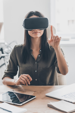 interactivity: It seems you can touch it. Confident young woman in virtual reality headset pointing in the air while sitting at her working place in office