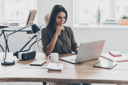 New solution every day. Confident young woman in smart casual wear working on laptop while sitting at her working place in office Stockfoto
