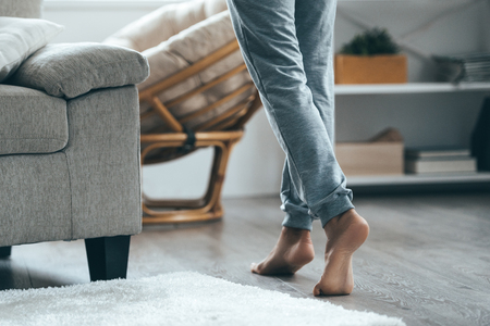 Warm floor concept. Close-up of female legs stepping by hardwood floor at home