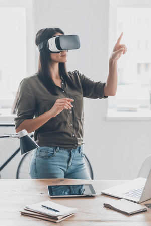 Future is now. Confident young woman in virtual reality headset pointing in the air while standing near her working place in office Stock Photo