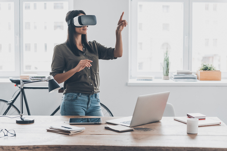interactivity: Innovation in business. Confident young woman in virtual reality headset pointing in the air while standing near her working place in office Stock Photo