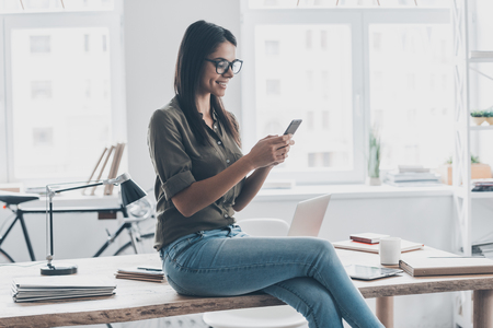 confident woman: Typing business message. Confident young woman in smart casual wear holding smart phone and looking at it with smile while standing near her working place