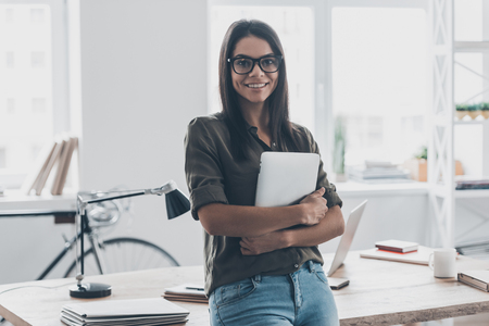 casual woman: Confident businesswoman. Confident young woman in smart casual wear holding digital tablet and smiling while standing near her working place