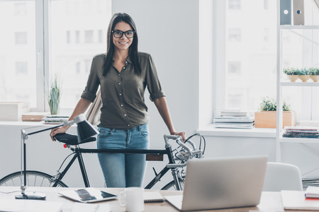 green office: Thinking green. Confident young woman in smart casual wear leaning at her bicycle while standing near her working place in office