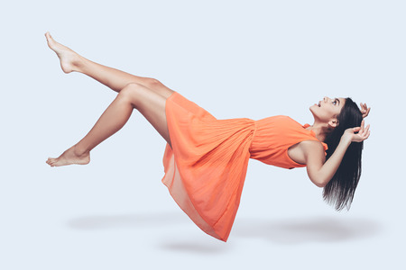 adult woman: Beauty in mid-air. Full length studio shot of attractive young woman in orange dress hovering in air and looking surprised Stock Photo