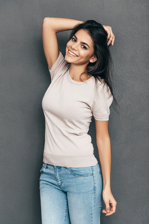 only adult: Candid and beautiful. Attractive young woman in casual wear holding hand in hair and smiling while standing barefoot against grey background Stock Photo