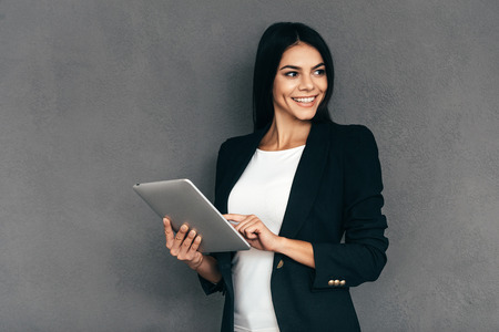 confident business woman: Confident business expert. Attractive young woman in smart casual wear working on digital tablet and smiling while standing against grey background