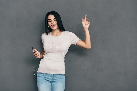 donna che balla: Il tempo per la musica! Attraente giovane donna sorridente in cuffie che tengono telefono intelligente e gesticolando mentre in piedi su sfondo grigio Archivio Fotografico