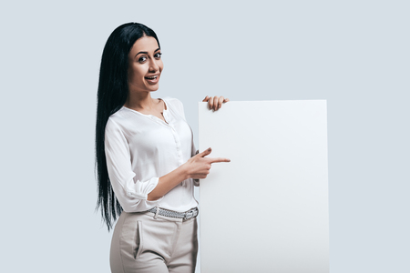 woman pointing: Place new ideas here! Young confident woman in white shirt pointing on blank flipchart while standing against grey background