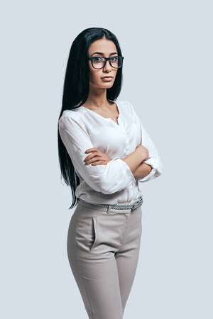 adult student: Time to make important decision. Confident young woman in a white shirt and glasses keeping arms crossed while standing against grey background