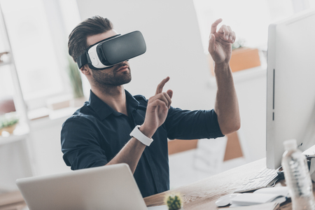 handsfree device: It is so real! Handsome young man in VR headset gesturing and smiling while sitting in creative office Stock Photo