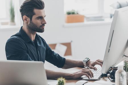 Drukke werkdag. Knappe jonge man werken op de computer tijdens de vergadering op zijn werkplek in het kantoor aan huis