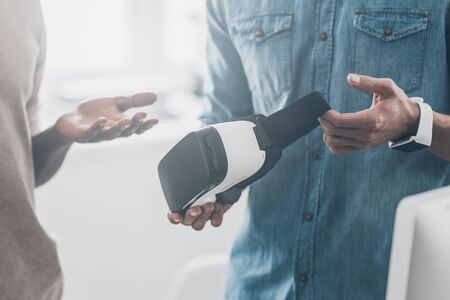 handsfree device: Amazing technology!  Two young successful men talking while one of them holding VR headset
