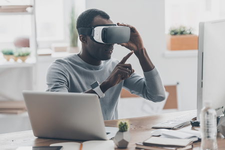 digitally generated image: Virtual work. Handsome young African man in VR headset pointing in the air while sitting at the desk in creative office Stock Photo