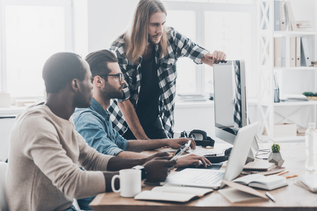 Focusing on the details. Group of young business people discussing something while sitting together and looking at the monitor Stock Photo