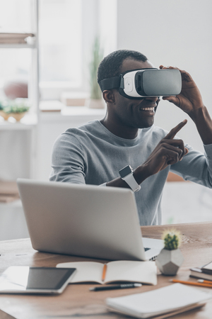 handsfree device: Everything is so real! Handsome young African man in VR headset gesturing and smiling while sitting at the desk in creative office