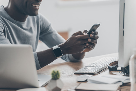 handsfree device: Pleasant moments. Close-up of handsome young African man typing a message on the phone and smiling while sitting at the desk in creative office