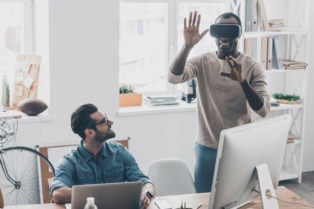 handsfree device: It is so real!  Two young successful men in casual wear working in creative office while one of them standing in VR headset  Stock Photo
