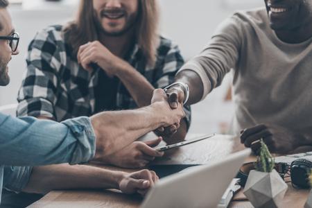 personas comunicandose: Reunión de negocios. Primer plano de los jóvenes se comunican entre sí en la oficina mientras que dos hombres dándose la mano y sonriendo