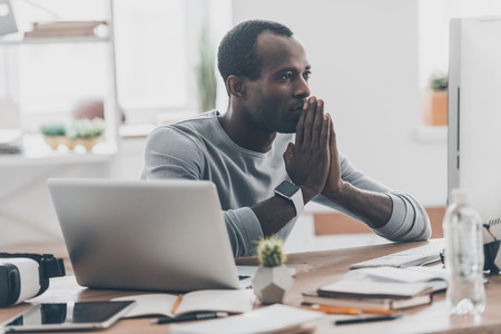 handsfree device: Focusing on work. Handsome young African man holding hands together while sitting at his working place in modern office