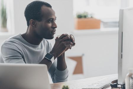 Morgenkaffee genießen. Durchdachter junger afrikanischer Mann, der eine Schale hält und den Computermonitor beim Sitzen am Schreibtisch im kreativen Büro betrachtet