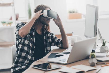 In my virtual world. Handsome young man with long hair adjusting his VR headset while sitting at his desk in creative office Stock Photo