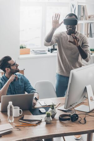 handsfree device: Enjoying new reality!  Two young successful men in casual wear working in creative office while one of them standing in VR headset