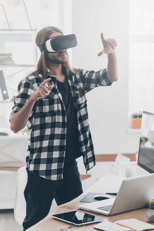 Enjoying new reality. Handsome young man with long hair in virtual reality headset gesturing while standing in creative office Imagens