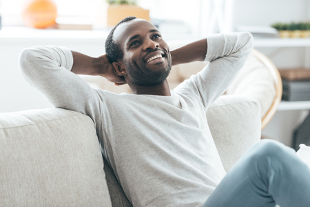 hands on head: Relaxing at home. Handsome young African man holding hands behind head and smiling while sitting on the sofa at home